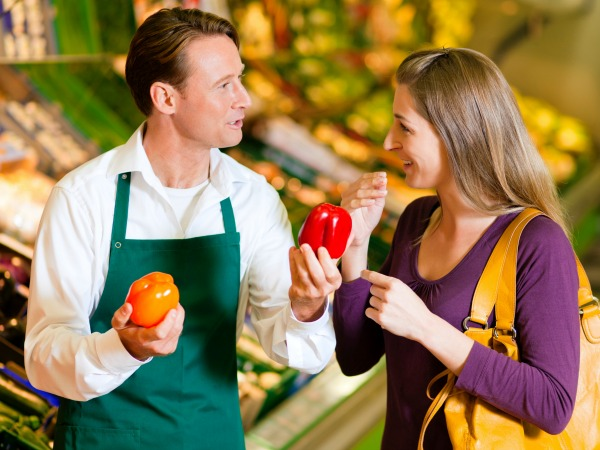Man helping woman with vegetable selection at grocery store