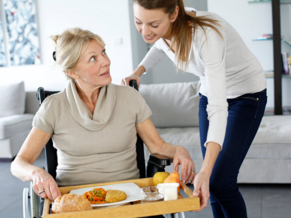 Woman giving food tray to woman in wheel chair - What Are the Primary Nutritional Issues for a Patient with Parkinson