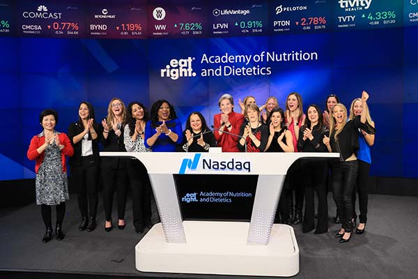 The Academy of Nutrition and Dietetics' [president and members standing by a podium at NASDAQ.